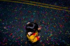 Children and parents alike were dancing in a street covered in confetti after the parade to celebrate the Chinese new year in Chinatown, Los Angeles, Calif. on Feb. 9, 2008. (Photo by Emily Ray/Brooks Institute of Photography, ©2008)